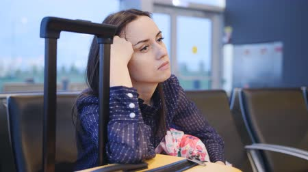 The delay of the flight. A woman waiting at the airport for the start of the check, looks at his watch and misses. Stok Video