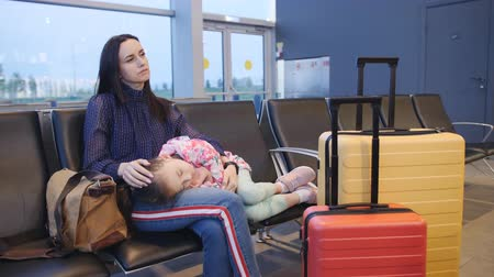 Daughter sleeping on the arms of my mother in the airport lobby. Tired girl sleeping on the arms of my mother at the airport.