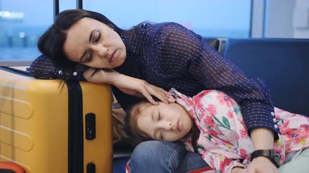 Mom is sleeping in the airport leaning on a suitcase and holding on hands little daughter sleeping.