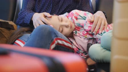 Close-up daughter sleeps in the lap of the mother at the airport. Tired daughter is Napping and the lap of the mother awaiting the start of check-in.