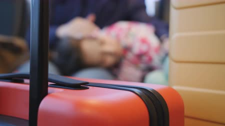 Fatigue at the airport. Woman with her daughter waiting for a transplant at the airport. The suitcase is in focus, sleeping daughter in the blur.