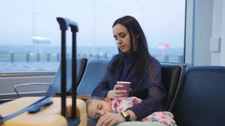 The woman awaits the start of check-in at the airport, sitting on a chair and drinking coffee. Little girl sleeps on her mothers lap.