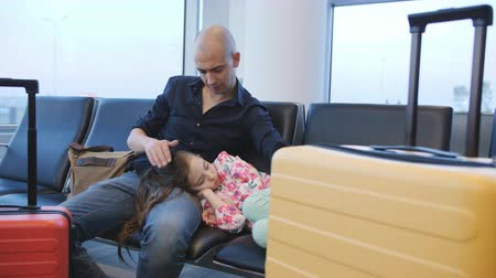 antecipação : Male father stroking the sleeping child sitting in the airport waiting for the delayed departure.