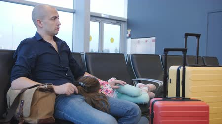 Father with sleeping on his hands daughter sitting at the airport waiting for the postponed departure
