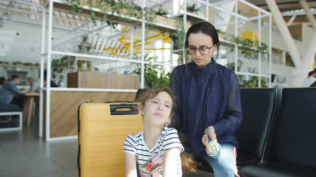 Mom combs her hair a little cranky daughter in the airport lobby.