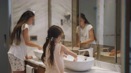 Children brush their teeth. Two sisters in the bathroom before the mirror brush their teeth.