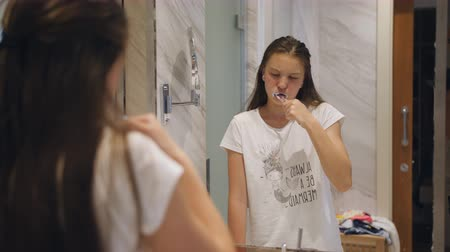 Teenage girl brushing her teeth in front of the mirror in the bathroom.