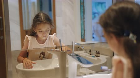 Little girl brushing her teeth in front of the mirror in the bathroom. Stok Video