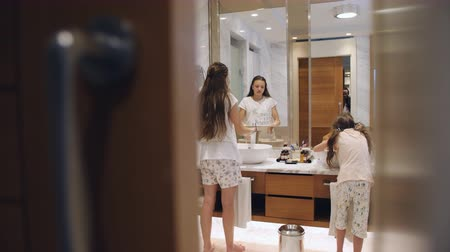 escova de dentes : Two sisters with long hair wearing nightdresses walking into bathroom and brushing their teeth before mirror