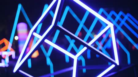 Glowing geometric shapes adorn the scene at night party in the open air.