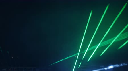 Laser show in a nightclub under the open sky. Laser beams and strobe lights in the night sky.