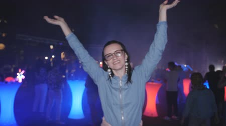 Woman in glasses is dancing night at the disco party. Dancing people disco lights and smoke.