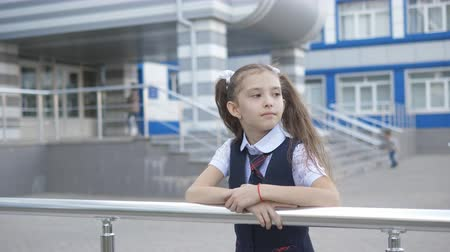 uniforme : Portrait shot of the pretty little girl in the school uniform in the school yard against the building of a primary school.