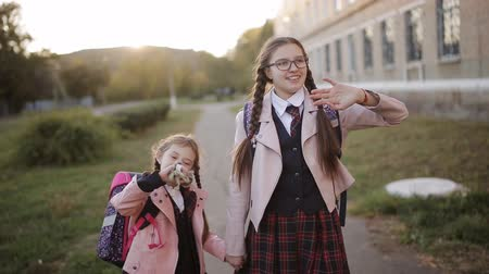 отпрыск : Mom meets her daughters at sunset near the school after school.