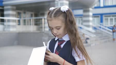 samenstellen : Student-centered elementary school in school uniform writes or draws something in a notebook near the school building. Stockvideo