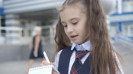 enthousiast : Cheerful elementary school Student in school uniform writes or draws something in a notebook near the school building.