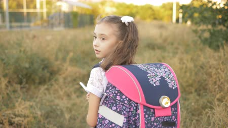aktetas : A little girl of 7 years old coming home from school with a briefcase on his shoulders, rear view.