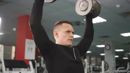overcome : Muscular man in the gym lifts weights sitting on a bench Stock Footage