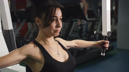 construção muscular : Sport activities in the gym. Woman bodybuilder. The exercises on the simulator.