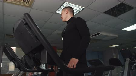 aerobic : Male athletic build, works out in the gym. A man trains on a treadmill at the athletic club.