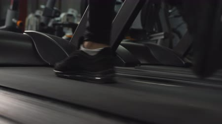 treadmill : Close up feet of man walking at brisk pace on treadmill at the gym, tracking left.