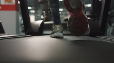 tornacipő : Slow motion footage of supposedly female legs in sneakers running on treadmill.
