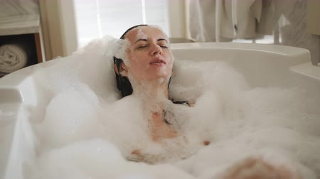 higiênico : Happy woman enjoy bath full of foam. Beautiful woman Enjoys Spa At Home