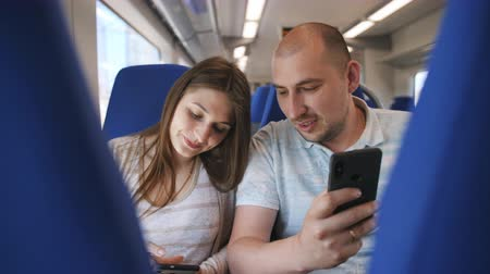 rekesz : A couple in love traveling in the train, sitting in comfortable chairs looking at the photos on the smartphone.