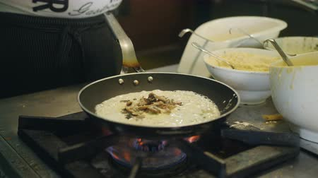sporák : The chef prepares pasta with mushrooms in a frying pan over high heat in an outdoor restaurant.