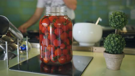 savanyúság : The chef works in the kitchen. In the foreground glass jar with marinated tomatoes, in the background cooking a cook in a restaurant. Stock mozgókép