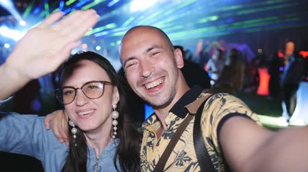 neon lights : Couple in a nightclub under the open sky, dancing having fun and relieve themselves on video. Stock Footage