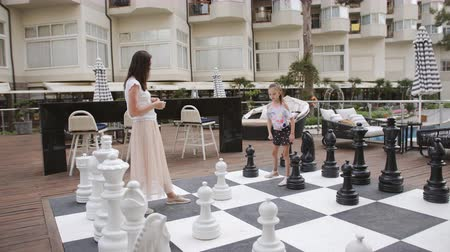 xadrez : Turkey, Belek - May 20, 2019. Papilon Zeugma Hotel. Mom and little daughter in nature play in big chess. Vídeos