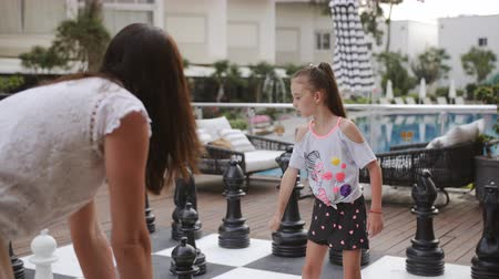 кусок : Turkey, Belek - May 20, 2019. Papilon Zeugma Hotel. The game of chess the huge figures outside. Mom and daughter fun play big chess. Стоковые видеозаписи