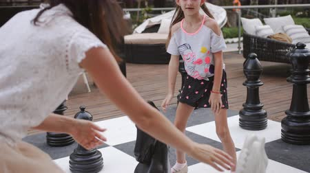 campo de batalha : Turkey, Belek - May 20, 2019. Papilon Zeugma Hotel. Playing outdoor chess large chess pieces. Mother and daughter playing chess with large figures.
