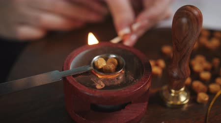 ceralacca : The woman melts the wax into a special furnace for applying a wax seal on the envelope.