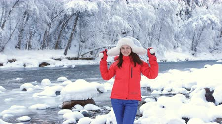 carelessness : Happy woman in winter landscape near a mountain river and enjoys the outdoors and is happy.