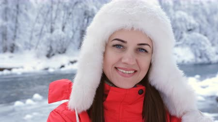 meseország : Close-up portrait of a beautiful woman in a red jacket and cap in the woods near the burrow of the river.