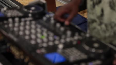 etnia africano : This is an African American male DJ, with a rack focus on his hands while turning dials.