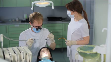 dentysta : Dentist and nurse begin treatment in dental office