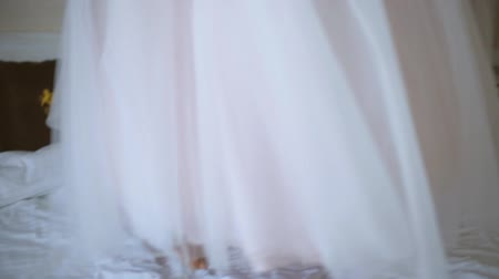 espartilho : cheerful and beautiful bride jumping on bed in room on wedding day