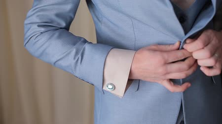 iyi giyimli : Buttoning a jacket. Stylish man in a suit fastening buttons on his jacket preparing to go out. Close up
