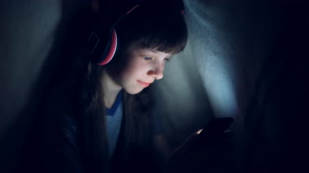 stories : the child in wireless headphones listens to music at night under a blanket and looks at the tablet