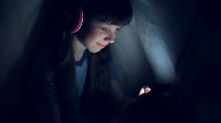 use computer : the child in wireless headphones listens to music at night under a blanket and looks at the tablet