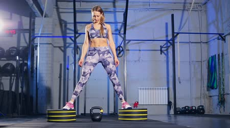 consciente : young woman in gray sportswear Begins doing exercise with weight. Cross fit
