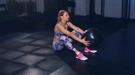 stomach : Beautiful muscular girl in gray tight tights sit ups with medicine ball throw. Cross fit