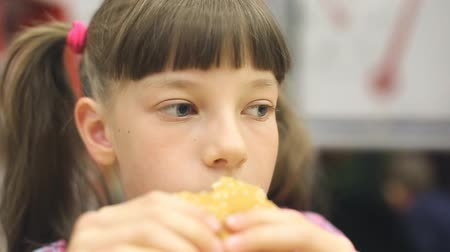 greedily : Young happy teenager eating tasty hamburger in fast food restaurant. Teen girl eating french fries for dinner at fast food cafe.
