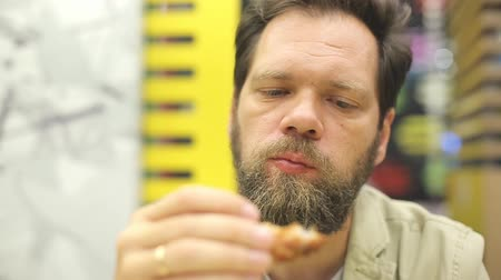 rántott : a bearded Caucasian man eats fried chicken wings and nuggets in a fast food cafe.
