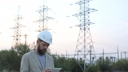 fitter : Station technical director with working drawings at nuclear power station. Worker in white helmet with engineering drawing near outdoor switchgear at nuclear power station.