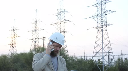rysunek techniczny : Station technical director in a white helmet stands near the power station and talking on the phone with the workers.
