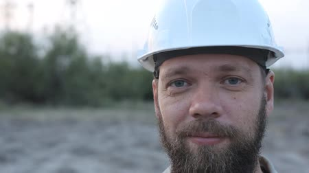 inspecting : portrait of a bearded man in a white helmet.